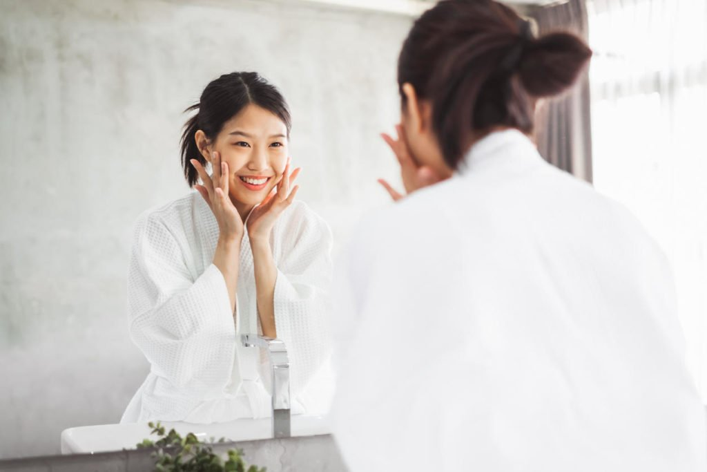 Asian woman cleaning face front of mirror, skin care and cosmetic removal